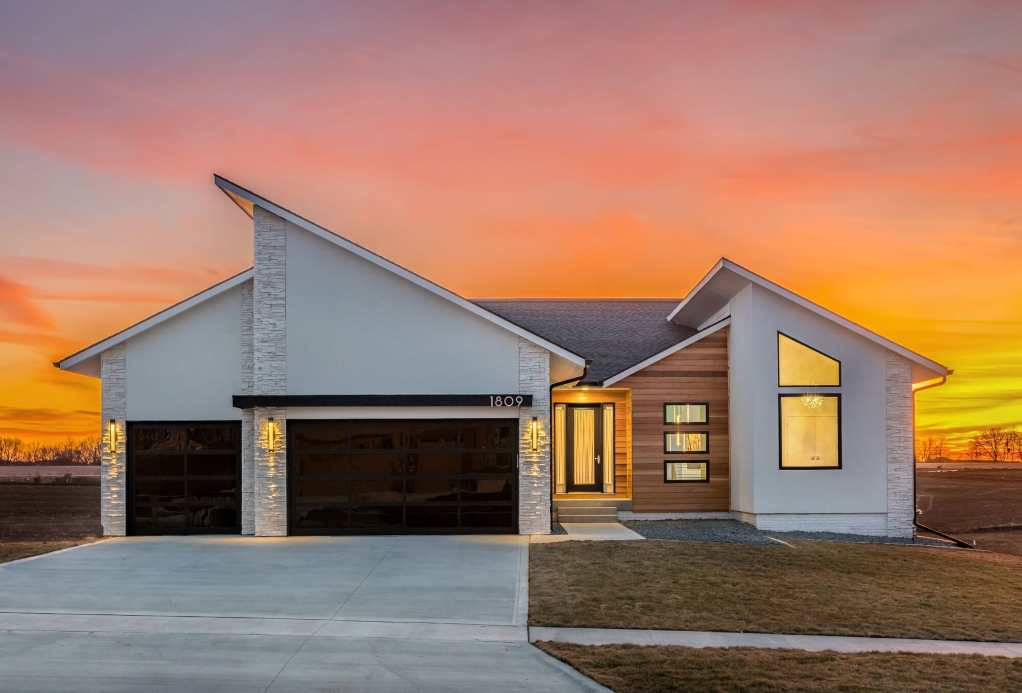 Modern-style custom-built home by Kruse Development with a white and wooden exterior, along with a sunset in the background.