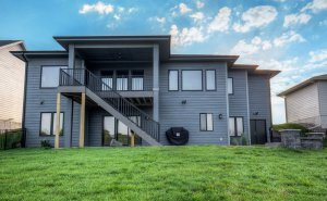 The back of an almost-black house with a deck that leads to a walkout basement, built by Kruse Development.