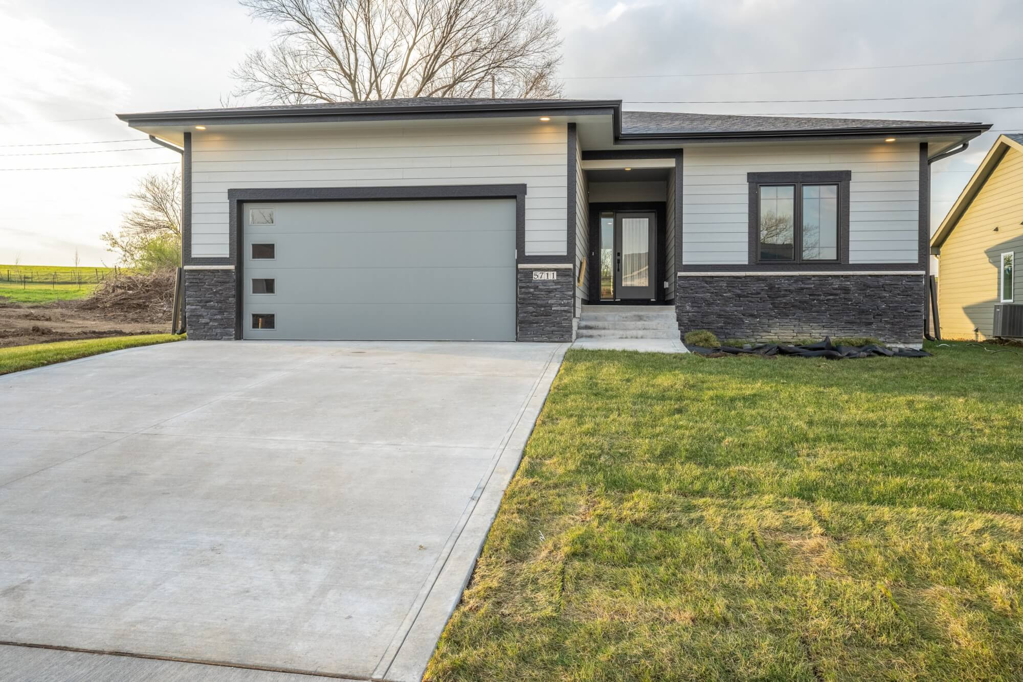 A home with white siding and grey stone, built by Kruse Development.