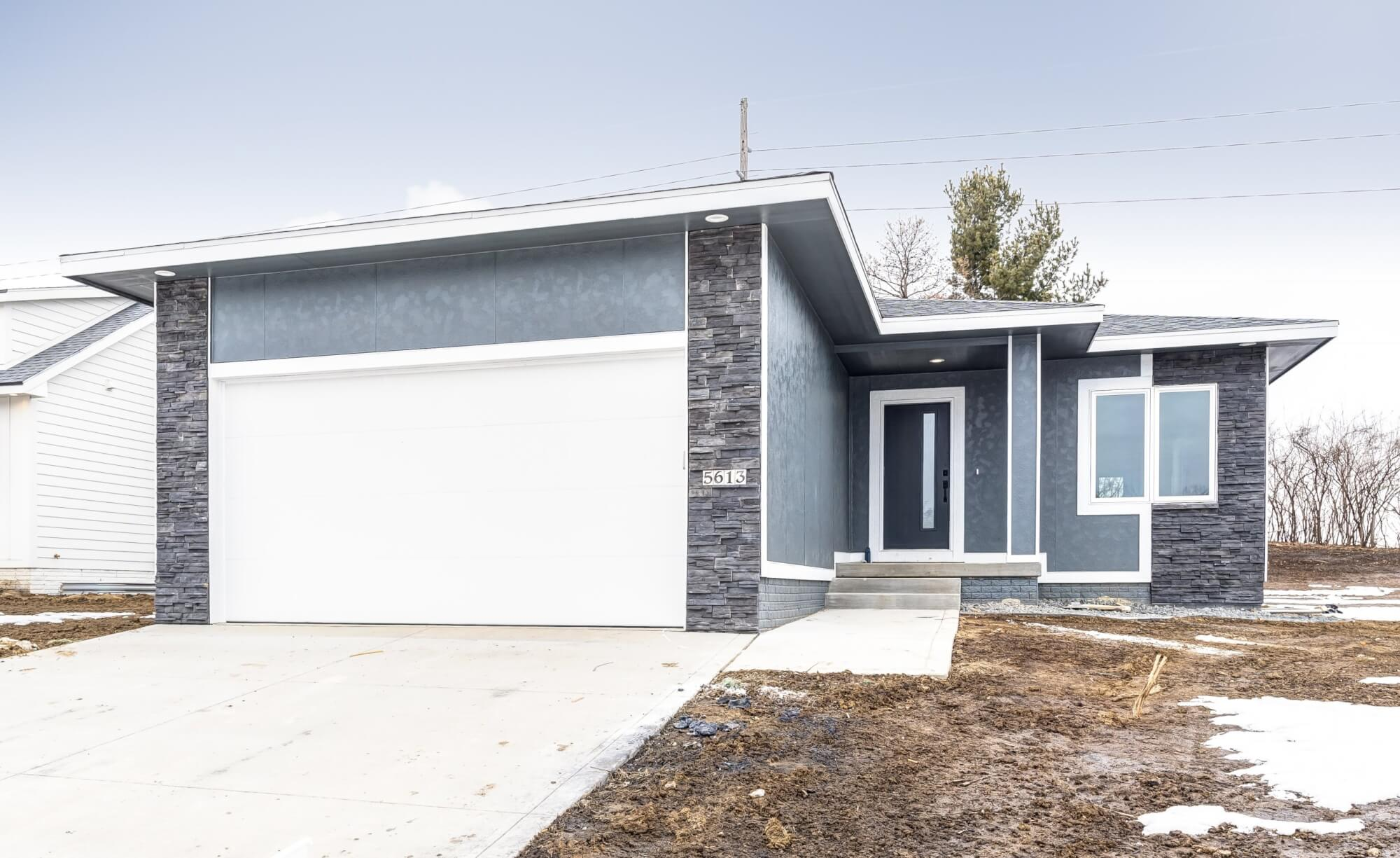 A grey house with metal and stone exterior, built by Kruse Development.