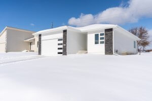 A picture of a one-story white and grey brick home built by Kruse Development.