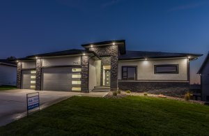 A grey stone house with outside lights on, built by Kruse Development.