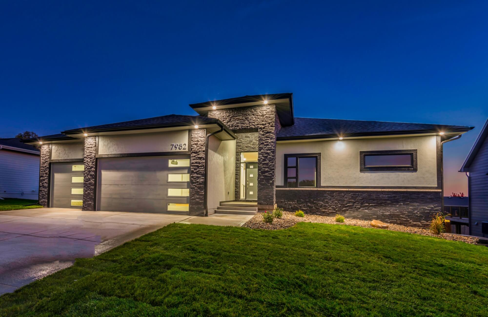 A grey stone house with exterior lights on at nightime, built by Kruse Development.