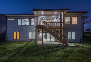 The backside of a house with lights on, built by Kruse Development.