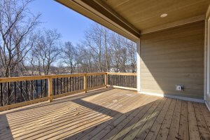A picture of a wooden balcony looking into the backyard, attached to a home built by Kruse Development.