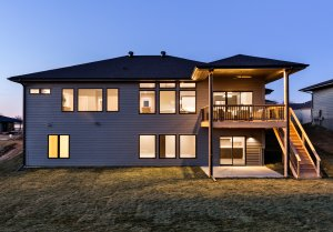 The backside of a lit-up house in the evening time built by Kruse Development.