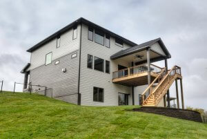 A two-story and walkout house with a deck and stairs that lead to the ground, built by Kruse Development.